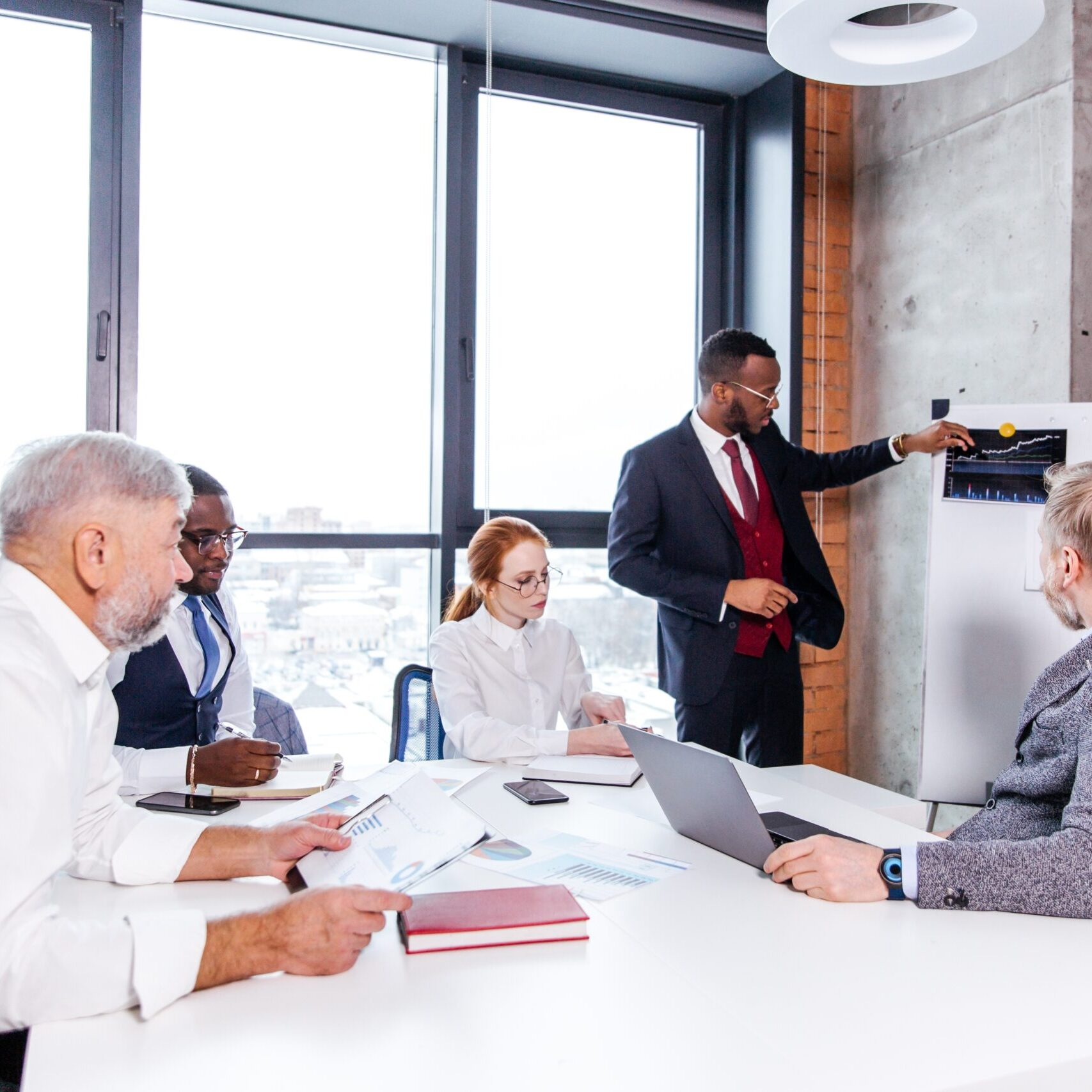 Multi-racial creative people in a modern office. African businessman presents new project standing at easel with economic development schedule